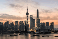 China, Shanghai skyline at dawn, showing the Huangpu river with passing cargo ships and Pudong skyline