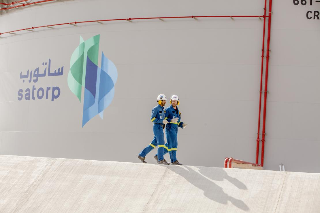 Operators in front of a crude oil storage tank at the Jubail refinery in Saudi Arabia.